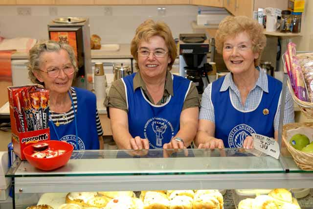 Three ladies in aprons behind a cafe counter
