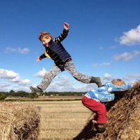 Me and Type 1 Diabetes - image of child jumping on hay bales