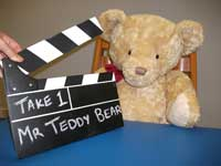 Teddy with a clapper board, about to be filmed