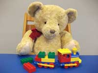 Teddy playing with a Duplo train