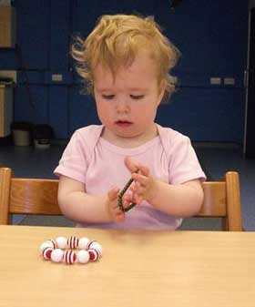 A child plays with a bead bracelet
