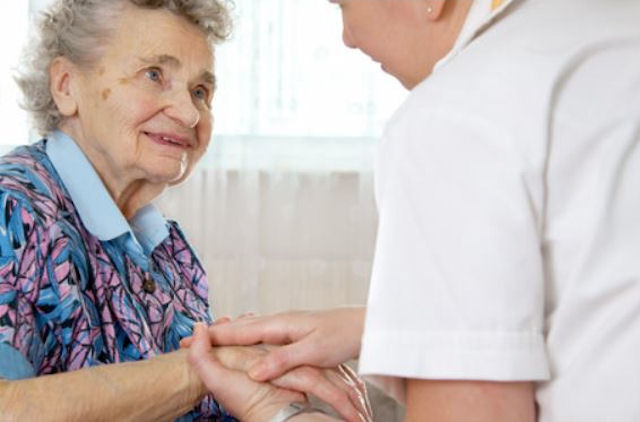 Elderly lady smiles at care worker