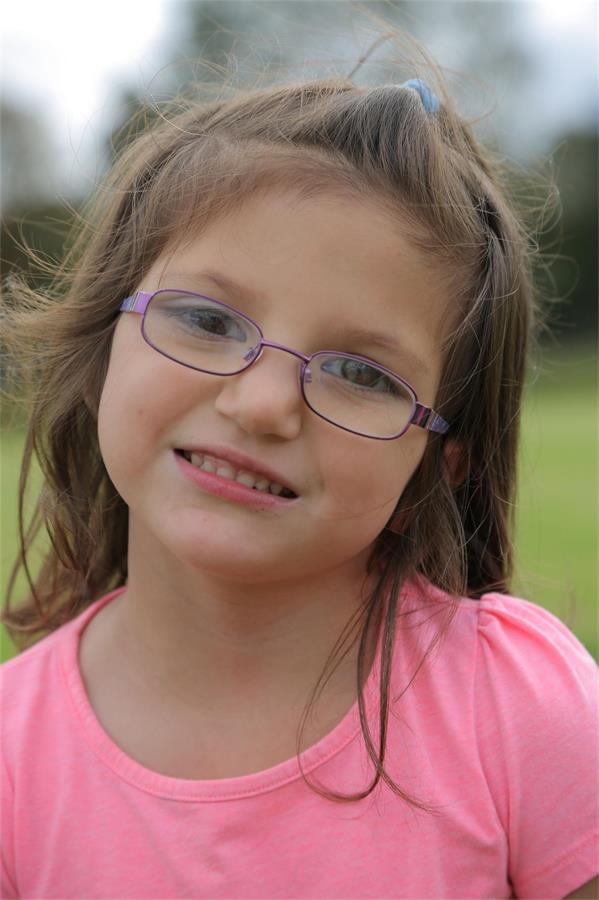 Smiling girl with glasses and a pink T shirt