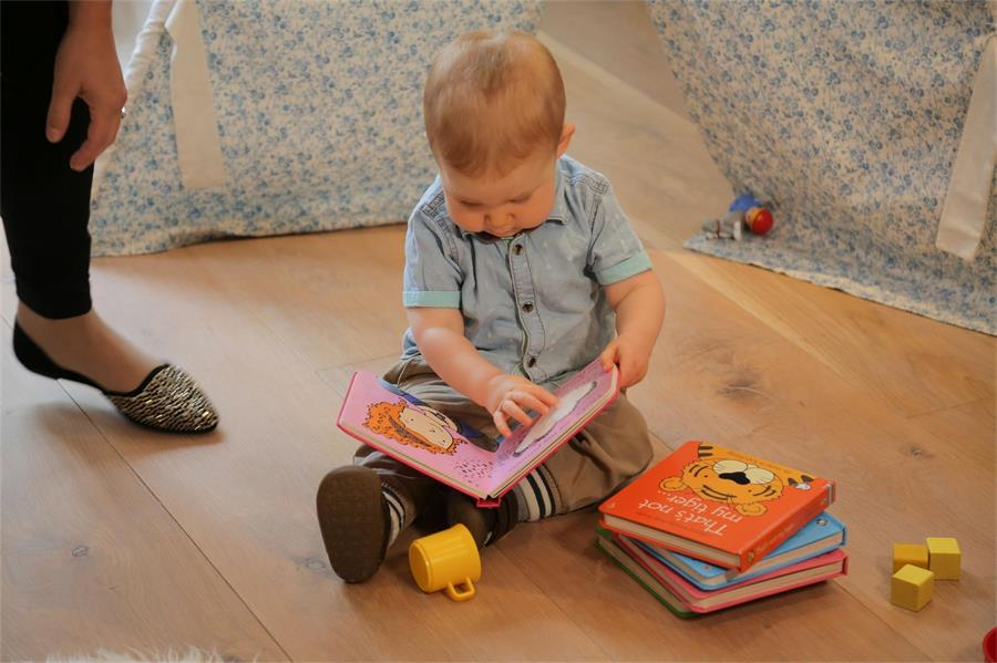 Baby in blue shirt sitting on the floor looking through a book