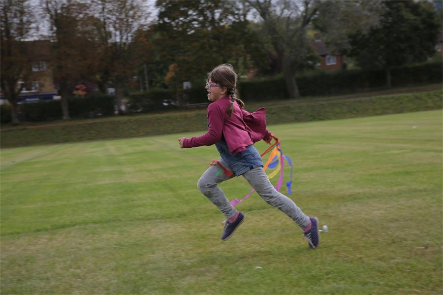 Girl running across grass waving a streamer