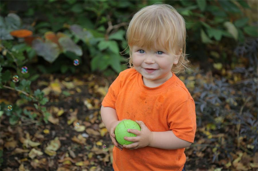Small child in orange holding a ball